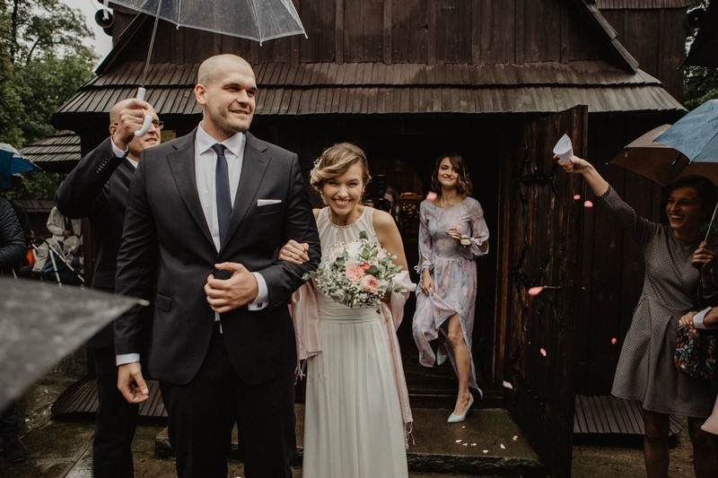 wyjście pary z kościoła deszczowy ślub parasole